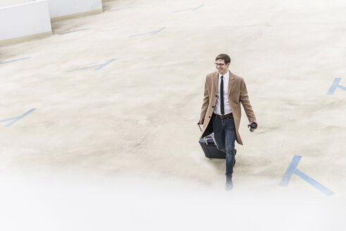 Smiling businessman with rolling suitcase walking at parking garage - UUF13435