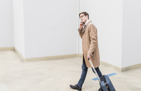 Businessman with rolling suitcase on the phone at parking garage - UUF13441