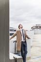 Businessman leaning back at parking garage - UUF13444