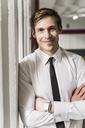 Portrait of smiling businessman wearing smartwatch - UUF13447