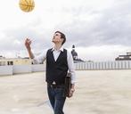 Businessman throwing up basketball at parking garage - UUF13450