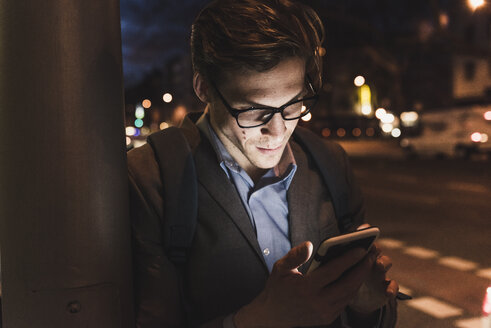 Businessman using cell phone on urban street at night - UUF13474