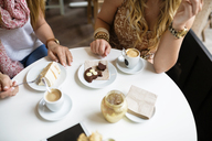 Midsection of women having desserts at coffee shop - CAVF40827