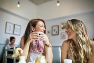 Beautiful female friends talking in coffee shop - CAVF40833