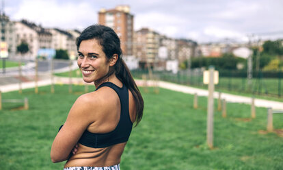Portrait of happy sportswoman looking over shoulder while standing at park - CAVF40890