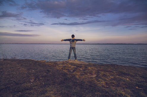 Rear view of boy with arms outstretched standing against sea and cloudy sky during sunset - CAVF40911