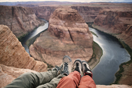 Low section of couple sitting on mountain by Horseshoe Bend - CAVF40923