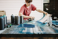 Woman spraying paint on cardboard at table - CAVF40965