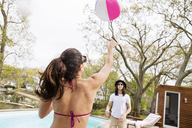 Friends playing with beach ball at poolside - CAVF41019
