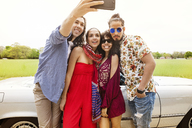 Man clicking selfie with friends against car at field - CAVF41112
