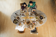 Overhead view of friends toasting drinks at dining table - CAVF41142