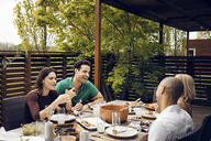 Cheerful friends having meal at outdoor table - CAVF41145