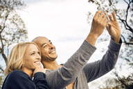 Couple taking selfie against clear sky - CAVF41193