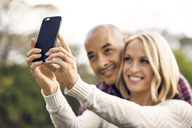 Smiling couple clicking selfie with smart phone - CAVF41235
