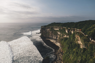 Scenic view of cliff by sea against cloudy sky - CAVF41246