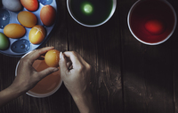 Cropped hands of woman making Easter eggs with dye on table at home - CAVF41282