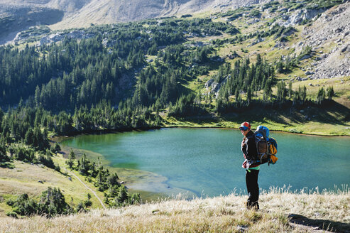 Smiling woman carrying backpack standing against lake in mountain - CAVF41402