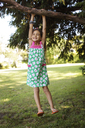 Cheerful girl hanging from branch on grassy field at park - CAVF41471