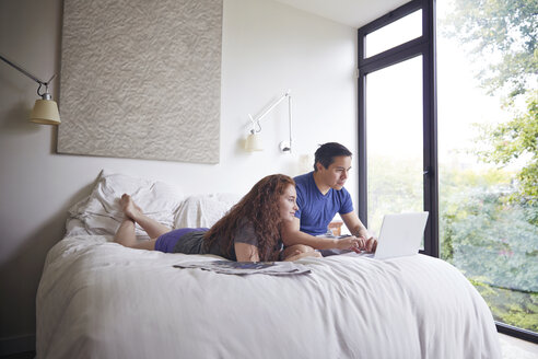 Couple looking at laptop computer while resting on bed by window - CAVF41561