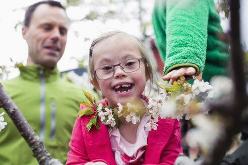 Portrait of happy handicapped girl with father and brother in yard - MASF04686