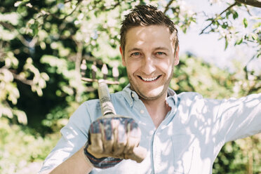 Portrait of happy man carrying gardening fork on shoulder at yard - MASF04689