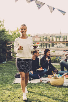 Portrait of happy woman with breakfast walking at rooftop party - MASF04695