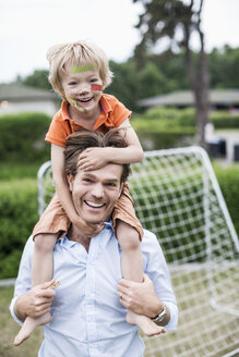 Portrait of happy father carrying injured boy on shoulders - MASF04704