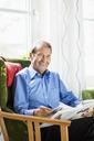 Portrait of happy senior man reading book at nursing home - MASF04710