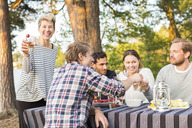 Portrait of happy woman holding beer glass while standing by friends having lunch at picnic table - MASF04719