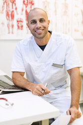 Portrait of happy male orthopedic doctor sitting at desk in clinic - MASF04722
