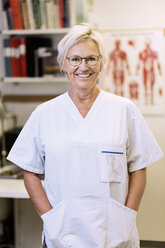Portrait of happy senior orthopedic surgeon standing with hands in pockets in clinic - MASF04725