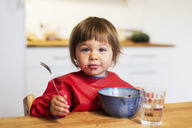 Portrait of little girl with messy mouth eating fruit salad at home - MASF04734