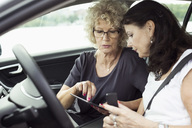 Senior female friends using digital tablet in car - MASF04743