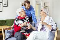 Senior woman talking to man while knitting at nursing home - MASF04767