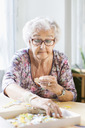 Senior woman assembling jigsaw pieces at table in nursing home - MASF04770