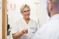 Senior doctor talking to man at orthopedic clinic - MASF04779