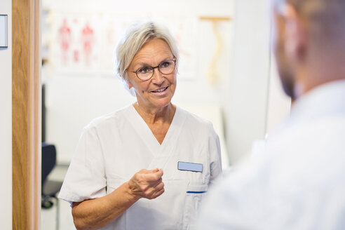 Senior doctor talking to man at orthopedic clinic - MASF04779