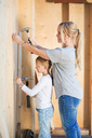 Side view of mother and daughter using hammers at house during home improvement - MASF04785