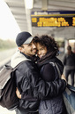 Side view portrait of happy couple embracing on subway platform - MASF04788