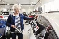 Senior woman admiring car in dealership store - MASF04797