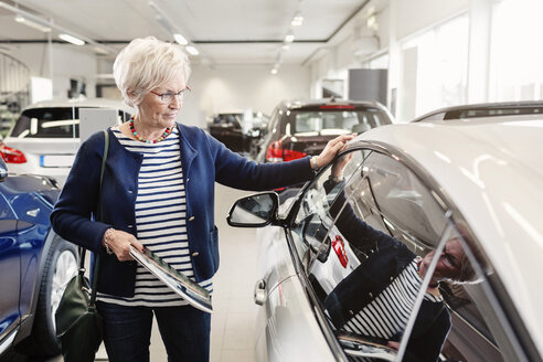 Senior woman admiring car in dealership store - MASF04797