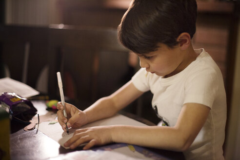 Boy drawing on paper at home - CAVF41688