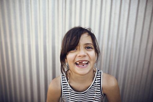 Portrait of happy girl standing against shutter - CAVF41730