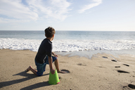 Boy looking at sea while sitting with bucket on beach during sunny day - CAVF41739
