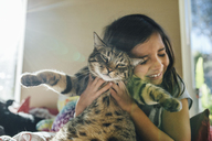 Happy girl with cat on bed at home - CAVF41757