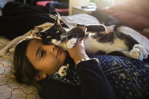 Girl with cat relaxing on bed at home - CAVF41763