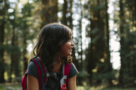 Happy girl with backpack looking away while sitting in forest - CAVF41775