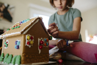 Low angle view of girl making gingerbread house on table at home - CAVF41784