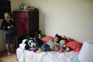 Girl getting dressed while sister using mobile phone on bed at home - CAVF41796