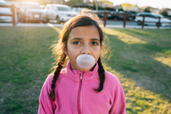 Portrait of girl blowing bubble gum while standing at park - CAVF41820